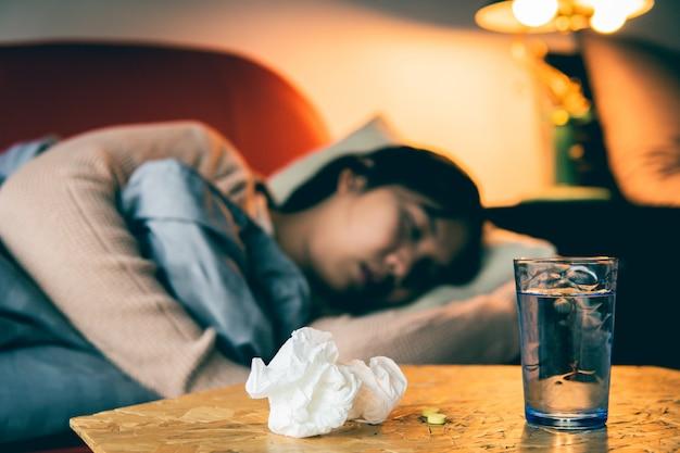 Kranke frau haben eine erkältung und schlafen auf dem sofa, selektiv und weich fokussiert.