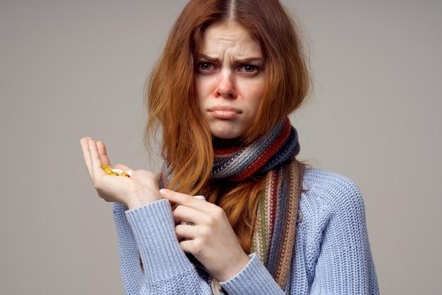 Kranke frau halstuch pillen in der hand isoliert hintergrund. foto in hoher qualität