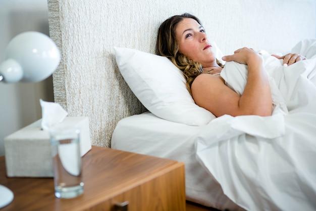 Kranke frau im bett liegend mit papiertaschentüchern und wasser neben sich