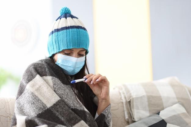 Kranke frau im hut unter decke in der medizinischen maske hält elektronisches thermometer in ihrer hand in der wohnung