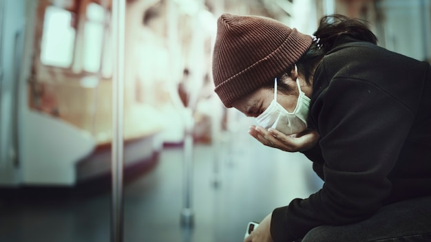 Kranke frau in einer maske, die in der öffentlichkeit während der coronavirus-pandemie hustet