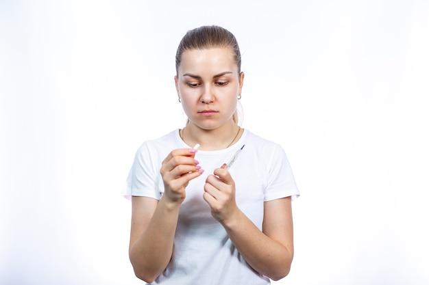 Kranke frau in medizinischer chirurgischer schutzmaske mit thermometer und pillen in der hand wird wegen des virus behandelt. selbstisolation und medikamente