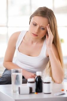 Kranke frau. junge frau, die sich die medikamente ansieht, die auf dem tisch liegen, während sie in ihrer wohnung im bett sitzt