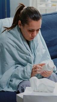 Kranke frau liest etikett auf einer flasche pillen und medikamente