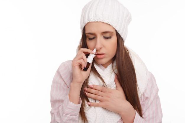 Kranke frau mit einem nasenspray