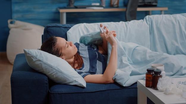 Kranke frau ruht auf sofa und benutzt oximeter