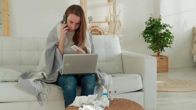 Kranke frau sitzt zu hause auf der couch ruft den arzt an und konsultiert medizintechnik-video-chat mit einem arzt, der zu hause behandelt wird, wenn sie krank sind
