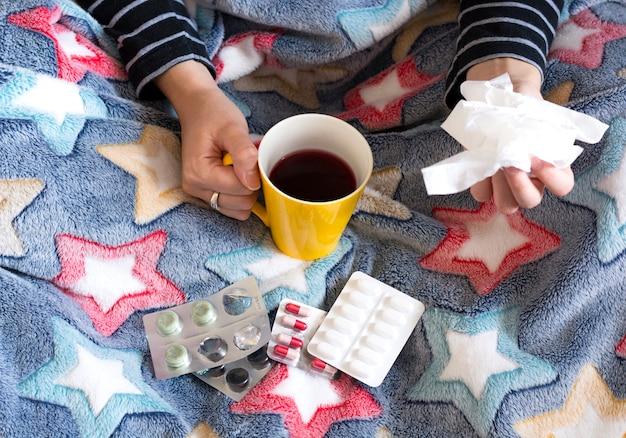 Kranke frau unter dem trinkenden tee der decke und nehmenpillen