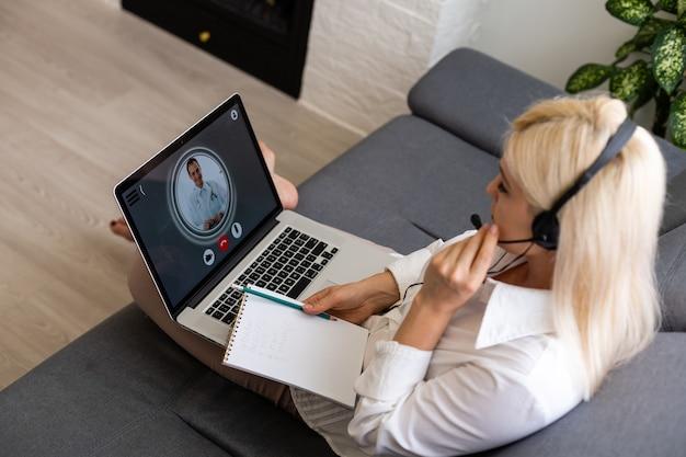 Kranke frau während der web-konsultation mit arzt, sitzt vor dem computer