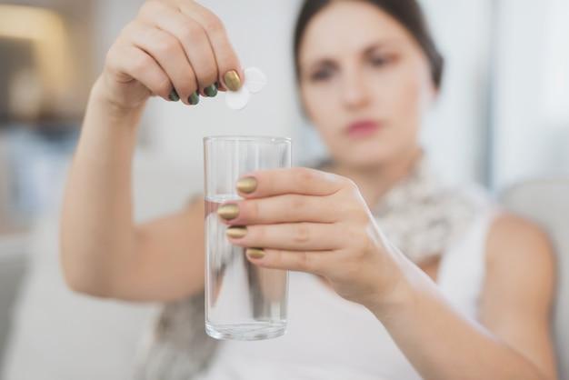 Kranke frau wirft zwei tabletten in ein glas wasser.