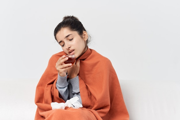 Kranke frau zu hause mit einer decke bedeckt, die tee trinkt