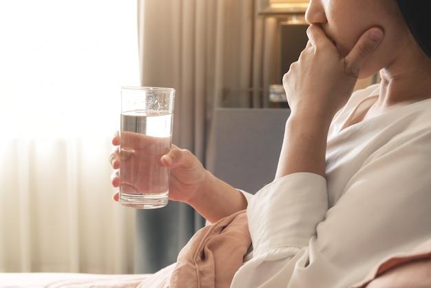 Kranke frauen hand halten ein glas wasser, gesundheitswesen und medizin wiederherstellungskonzept