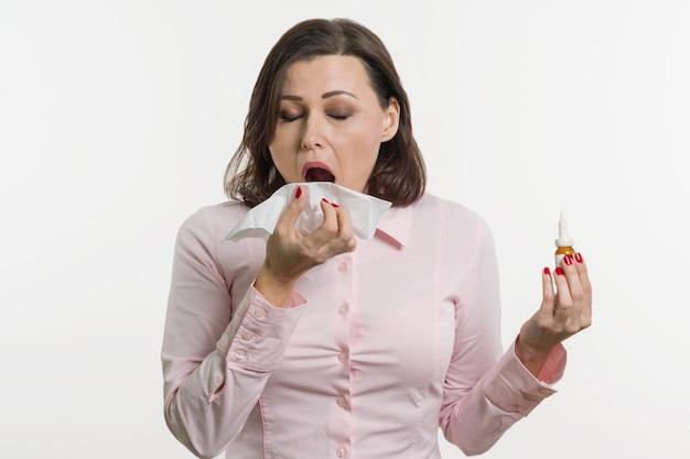 Kranke geschäftsfrau, die ein taschentuch und einen nasenspray hält.