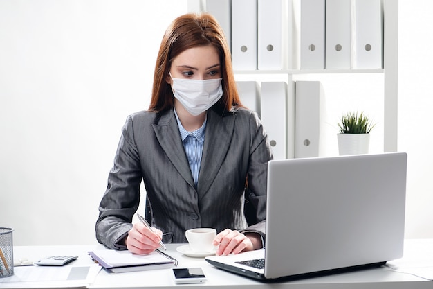 Kranke geschäftsfrau in einer medizinischen schutzmaske im büro
