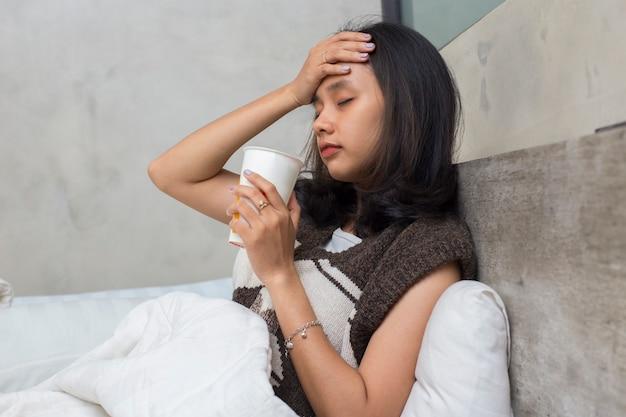 Kranke junge asiatische schöne frau, die wasser im bett trinkt