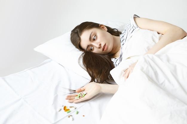 Kranke junge brünette frau, die morgen im bett verbringt, bündel von pillen auf ihrer hand betrachtet und über weißes blatt verschüttet