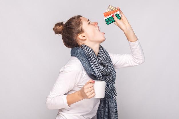 Kranke junge frau, die tasse mit tee, vielen pillen und antibiotika hält. studioaufnahme, auf grauem hintergrund isoliert