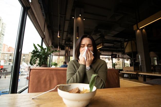 Kranke junge frau mit laufender nase kam in ein café.