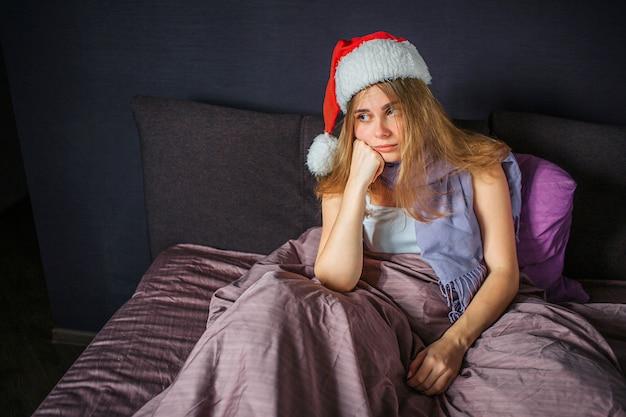 Kranke junge frau sitzt auf dem bett und sieht gerade aus. sie ist gelangweilt. frau hält hände unter kinn. sie hat weihnachtsmütze auf dem kopf.