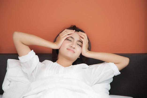 Kranke junge frauen auf dem bett mit kopfschmerzen, kater, schlaflosigkeit
