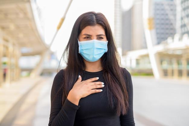 Kranke junge inderin mit maske, die halsschmerzen in der stadt draußen hat
