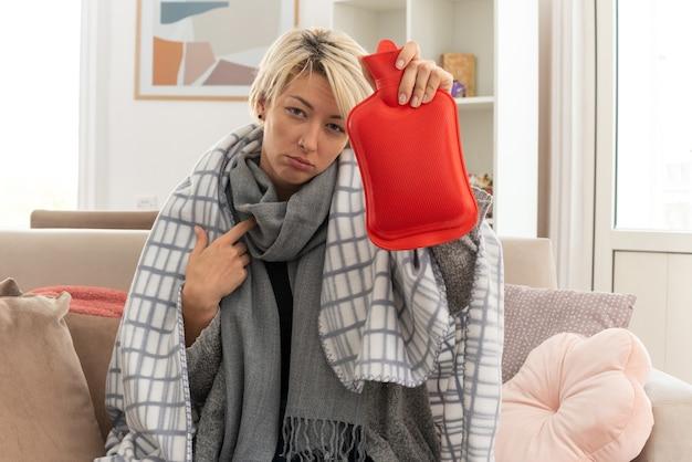 Kranke junge slawische frau mit schal um den hals, die in plaid gewickelt ist, eine wärmflasche hält und auf sich selbst zeigt, die auf der couch im wohnzimmer sitzt
