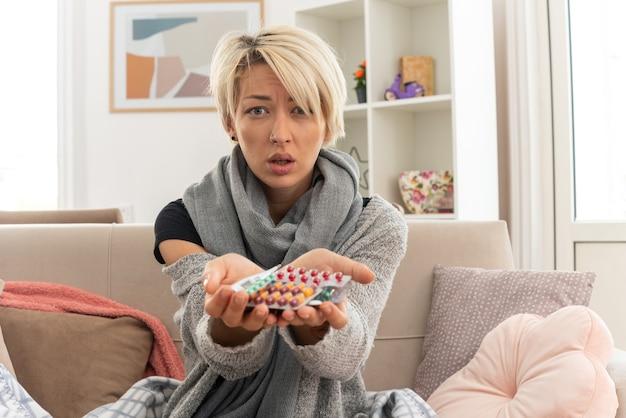 Kranke junge slawische frau mit schal um den hals, die in plaid gewickelt ist und medizinblisterpackungen hält, die auf der couch im wohnzimmer sitzen