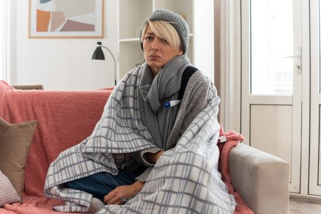 Kranke junge slawische frau mit schal um den hals, eingewickelt in karierte wintermütze, die ihre temperatur mit einem thermometer misst, das auf der couch im wohnzimmer sitzt