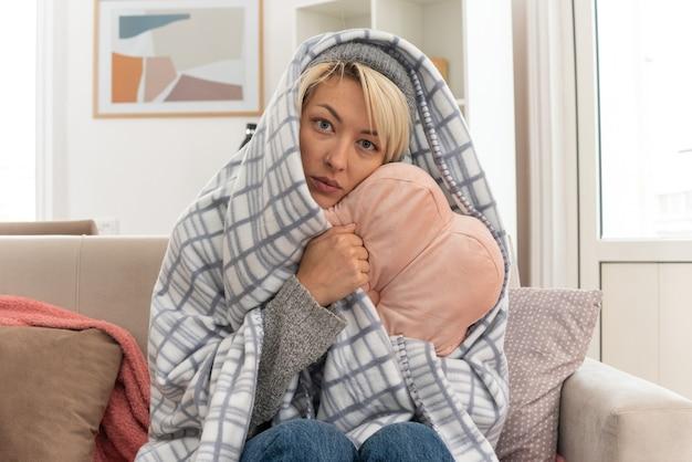 Kranke junge slawische frau mit schal um den hals in plaid gehüllt mit wintermütze, die kissen umarmt und in die kamera schaut, die auf der couch im wohnzimmer sitzt