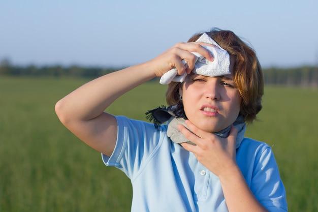 Kranke kranke junge frau in einem schal schwitzt, leidet unter einem hitzschlag. mädchen hat halsschmerzen draußen in einem sommerpark, feld. frau im fieber, reibt sich die stirn mit einem taschentuch