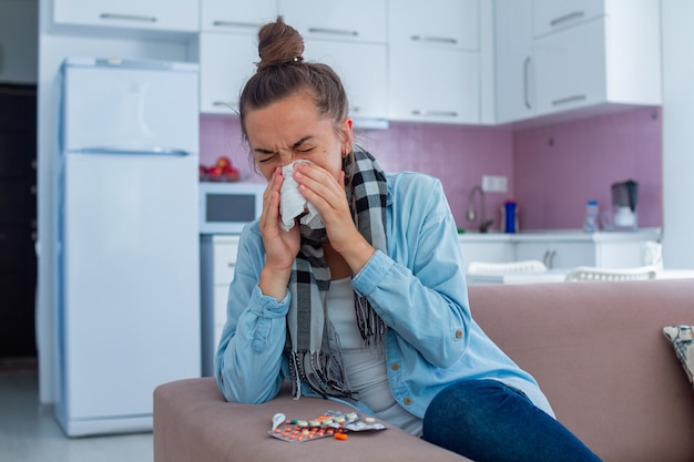 Kranke niesende frau im schal erkältet. kältebehandlung zu hause