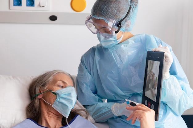Kranke patientin im bett im krankenhaus im gespräch mit der familie über eine tablette