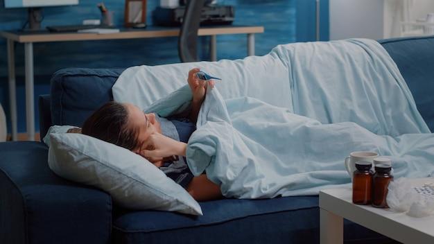 Kranke person, die auf der couch liegt und thermometer hält