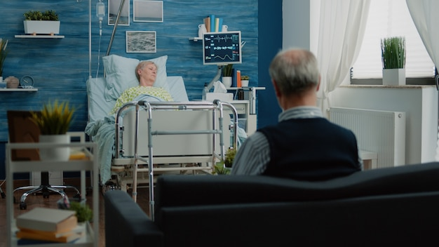 Kranke rentnerin ruht sich nach der operation im krankenhausbett aus