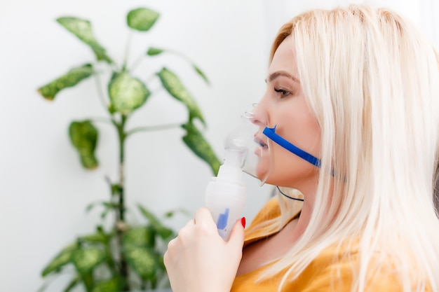 Kranke schöne frau hält nasenmaske mit atemproblemen im krankenhauszimmer. inhalationstherapie für frauenpatienten durch die maske des inhalators mit weichem rauch vom bronchodilatator.