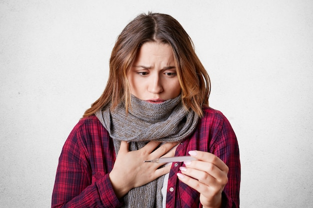 Kranke schöne frau schaut auf termometer, hat hohe temperatur, grippe, trägt warmen schal am hals wie halsschmerzen, schockiert