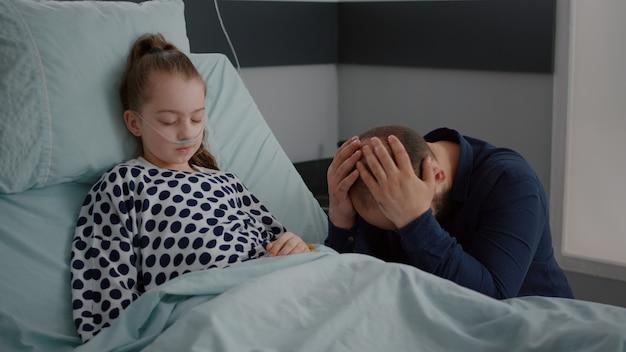 Kranke tochter des kleinen mädchens mit sauerstoff-nasenschlauch, die während der erholungsuntersuchung im bett schläft