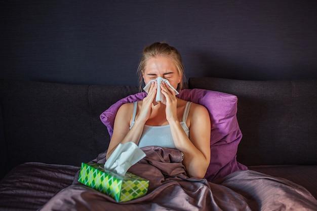 Kranke und kranke junge frau, die in weiße serviette niest. sie sitzt auf dem bett und ist mit einer seidendecke bedeckt. junge frau hat grüne schachtel taschentücher auf dem bett.