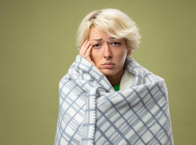 Kranke ungesunde frau mit kurzen haaren, die sich unwohl fühlen, eingewickelt in eine decke, die an grippe leidet und ihren kopf berührt, der über der hellen wand steht