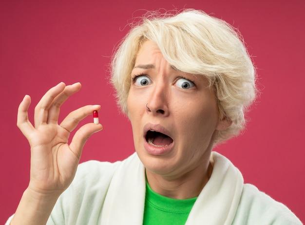 Kranke ungesunde frau mit kurzen haaren, die sich unwohl fühlen, nehmen gestresste und besorgte pille nehmen, die kamera betrachtet, die über rosa hintergrund steht