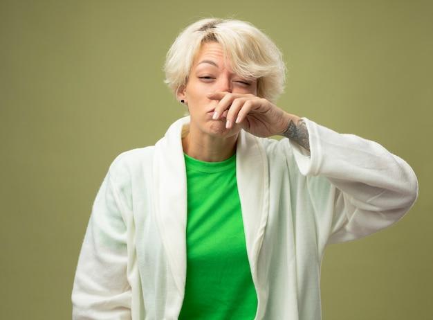 Kranke ungesunde frau mit kurzen haaren, die sich unwohl fühlen und ihre nase berühren, die über hellem hintergrund steht