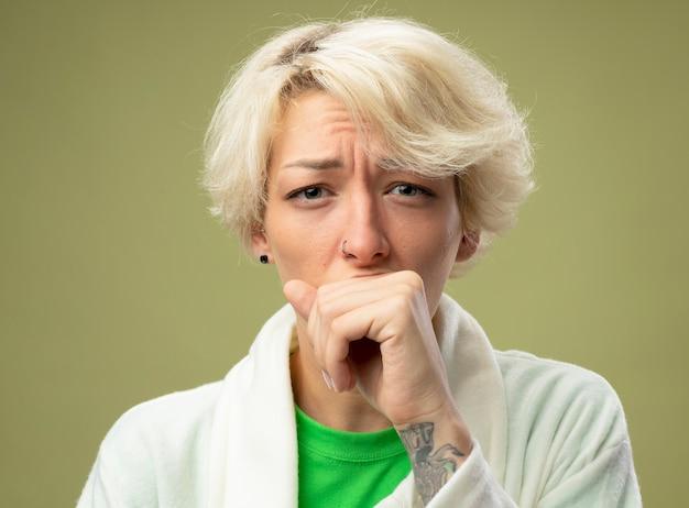 Kranke ungesunde frau mit kurzen haaren, die sich unwohl fühlen und über heller wand stehen