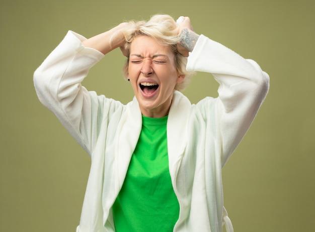 Kranke ungesunde frau mit kurzen haaren, die sich unwohl fühlen, wenn sie frustriert sind und ihr haar über eine helle wand ziehen