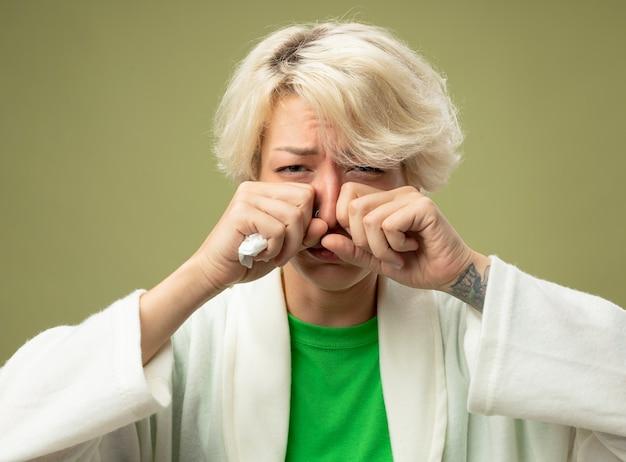 Kranke ungesunde frau mit kurzen haaren, die sich unwohl fühlen, wenn sie verärgert sind und ihre augen reiben, die an einer laufenden grippe-nase leiden, die über hellem hintergrund steht