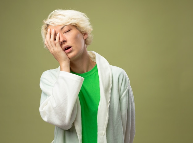 Kranke ungesunde frau mit kurzen haaren, die sich unwohl und müde fühlen, halten hand auf ihrem gesicht mit geschlossenen augen, die über lichtwand stehen