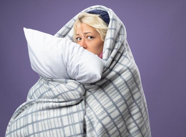 Kranke ungesunde frau mit kurzen haaren in warmem hut, eingewickelt in decke, die kissen hält, das sich unwohl fühlt mit besorgtem ausdruck besorgt über lila wand