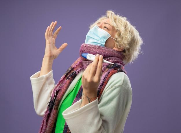 Kranke ungesunde frau mit kurzen haaren in warmem schal und gesichtsschutzmaske, die thermometer glücklich und aufgeregt über lila hintergrund hält