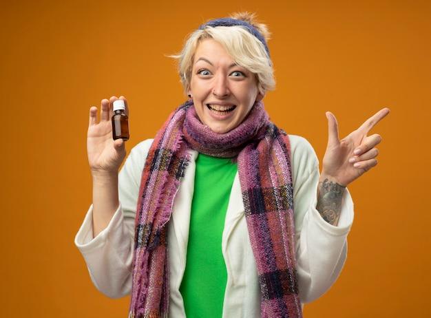 Kranke ungesunde frau mit kurzen haaren in warmem schal und hut, die medizinflasche hält, die mit zeigefinger zur seite zeigt lächelnd und sich besser fühlt, als über orange wand zu stehen