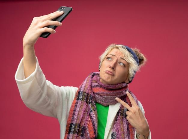 Kranke ungesunde frau mit kurzen haaren in warmem schal und hut, die sich besser fühlen, selfie unter verwendung des smartphones zu tun, das v-zeichen zeigt, das über rosa wand steht