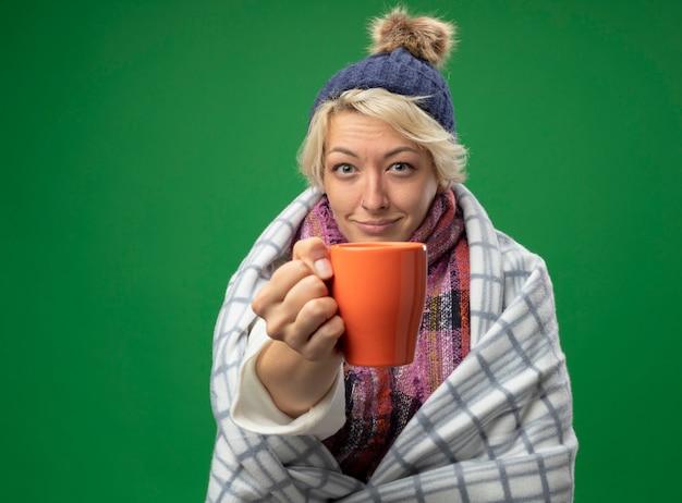 Kranke ungesunde frau mit kurzen haaren in warmem schal und hut, die sich besser in decke gewickelt fühlen, die tasse tee lächelnd über grünem hintergrund stehend hält